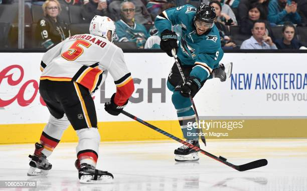 Evander Kane of the San Jose Sharks shoots the puck past Mike Giordano of the Calgary Flames at SAP Center on November 11 2018 in San Jose California