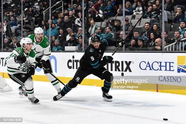 Evander Kane of the San Jose Sharks skates after the puck against Taylor Fedun and Radek Faksa of the Dallas Stars at SAP Center on December 13 2018...