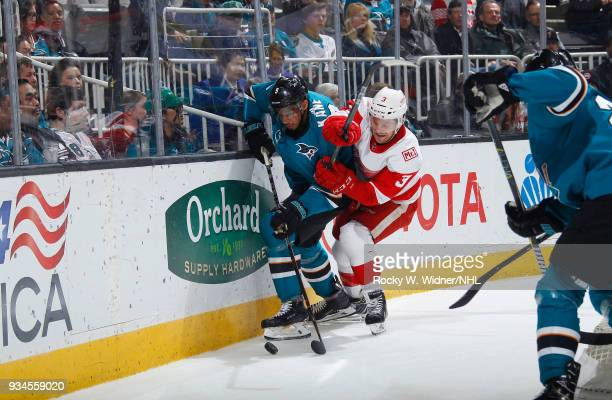 Evander Kane of the San Jose Sharks skates after the puck against Nick Jensen of the Detroit Red Wings at SAP Center on March 12 2018 in San Jose...
