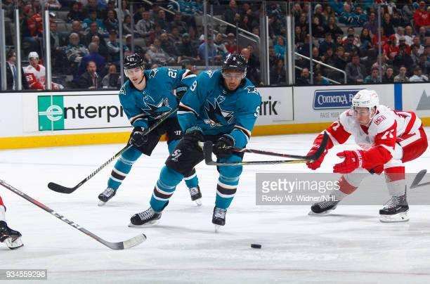 Evander Kane of the San Jose Sharks skates after the puck against Dylan Larkin of the Detroit Red Wings at SAP Center on March 12 2018 in San Jose...
