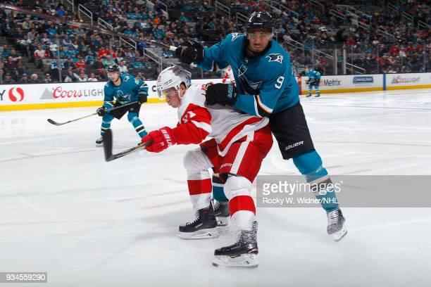 Evander Kane of the San Jose Sharks skates against Dylan Larkin of the Detroit Red Wings at SAP Center on March 12 2018 in San Jose California