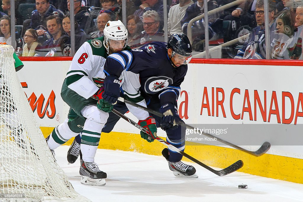 Evander Kane #9 of the Winnipeg Jets battles Marco Scandella #6 of the Minnesota Wild as they chase the puck along the boards during third period action at the MTS Centre on April 7, 2014 in Winnipeg, Manitoba, Canada. The Wild defeated the Jets 1-0.