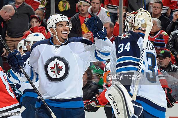 Evander Kane of the Winnipeg Jets celebrates with goalie Michael Hutchinson after defeating the Chicago Blackhawks 1-0 during the NHL game on...