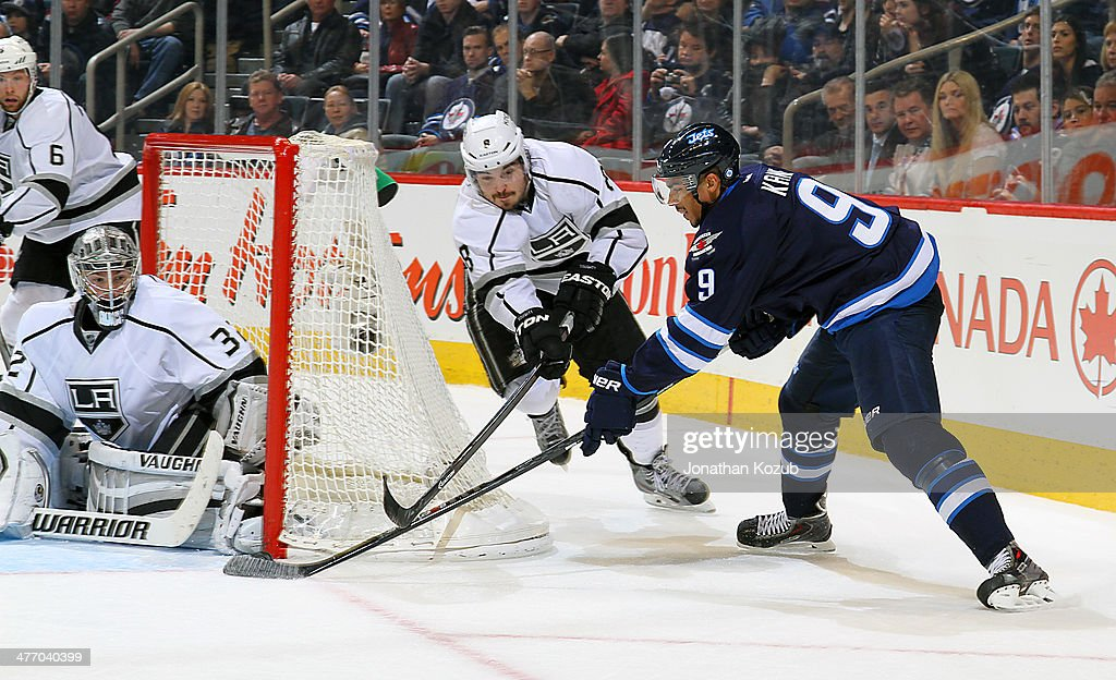 Evander Kane #9 of the Winnipeg Jets tries to score from the side of the net as goaltender Jonathan Quick #32 and Drew Doughty #8 of the Los Angeles Kings defend during third period action at the MTS Centre on March 6, 2014 in Winnipeg, Manitoba, Canada.