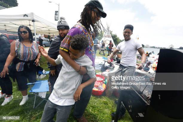 """Evander Woods, center, plays with his nephew Julian Cruc as chef Michael Woods, right, dances and barbecues at the same time at the """"BBQ-ing while..."""