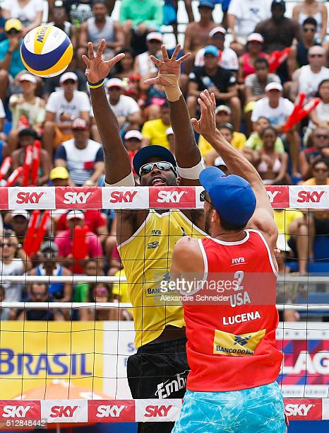 evandro Goncalves of Brazil blocks the ball against Nick Lucena of the United States during the golden medal match at Pajucara beach during day six...