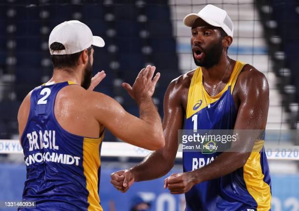 Evandro Goncalves Oliveira Junior and Bruno Oscar Schmidt of Team Brazil react against Team Poland during the Men's Preliminary - Pool E beach...