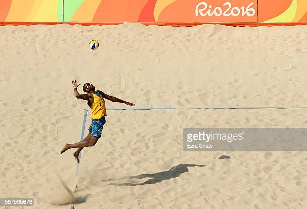 Evandro Goncalves Oliveira Junior of Brazil spikes the ball during the Men's Beach Volleyball Preliminary Pool D match against Chaim Schalk and Ben...