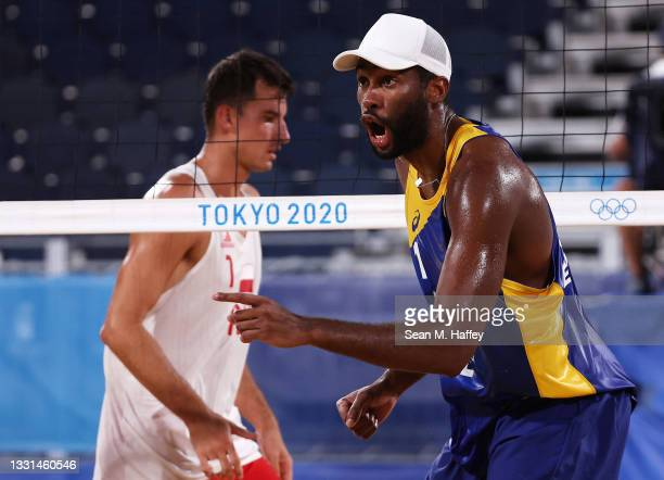 Evandro Goncalves Oliveira Junior of Team Brazil reacts against Michal Bryl of Team Poland during the Men's Preliminary - Pool E beach volleyball on...