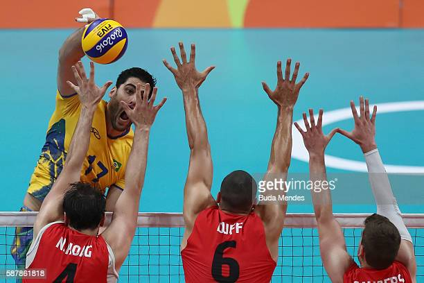 Evandro Guerra of Brazil spikes the ball against Nicholas Hoag Justin Duff and Tyler Sanders of Canada during the men's qualifying volleyball match...