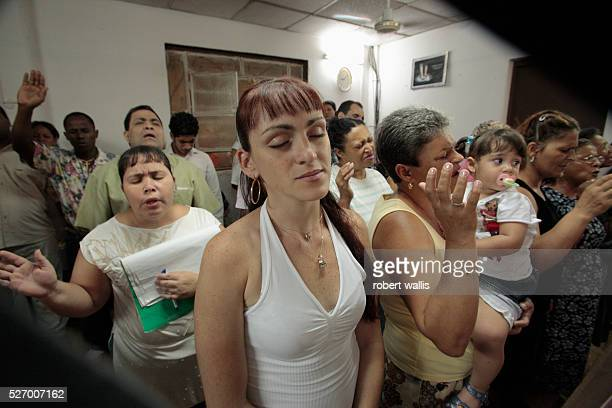 Evangelical Christians worship in a ground floor room in a residential building in old Havana Cuba legally bans house churches that are created by...