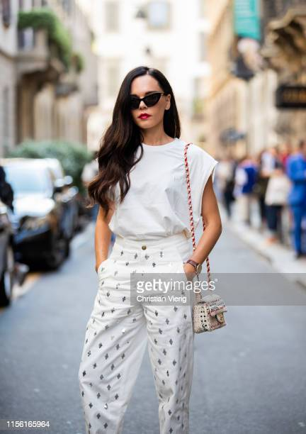 Evangelie Smyrniotaki is seen wearing sleeveless shirt white pants Chanel bag outside Versace during the Milan Men's Fashion Week Spring/Summer 2020...