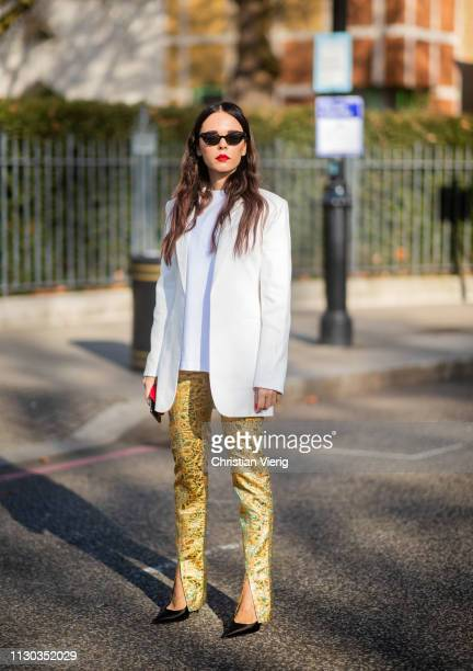 Evangelie Smyrniotaki is seen wearing yellow pants with print and slit outside Victoria Beckham during London Fashion Week February 2019 on February...