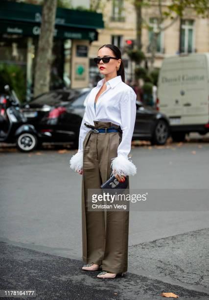 Evangelie Smyrniotaki seen wearing khaki belted high waist pants white button shirt black clutch sunglasses outside Valentino during Paris Fashion...