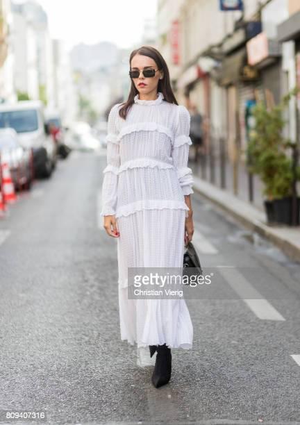 Evangelie Smyrniotaki wearing a white dress black boots and bag outside Maison Margiela during Paris Fashion Week Haute Couture Fall/Winter 20172018...