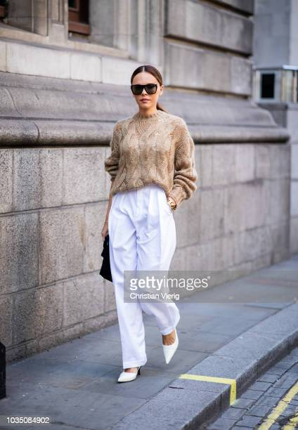 Evangelie Smyrniotaki wearing white pants beige knit is seen outside Erdem during London Fashion Week September 2018 on September 17 2018 in London...