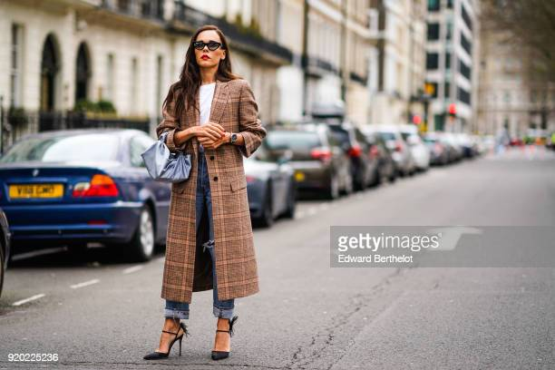 Evangelie Smyrniotaki wears a checked brown coat ripped jeans a blue bag a white top sunglasses during London Fashion Week February 2018 on February...