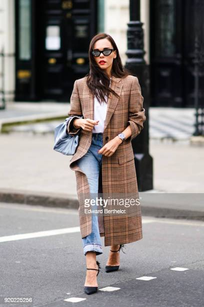 Evangelie Smyrniotaki wears a checked brown coat, ripped jeans, a blue bag, a white top, sunglasses, during London Fashion Week February 2018 on...