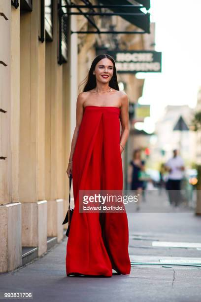 Evangelie Smyrniotaki wears a red offshoulder dress outside Valentino during Paris Fashion Week Haute Couture Fall Winter 2018/2019 on July 4 2018 in...