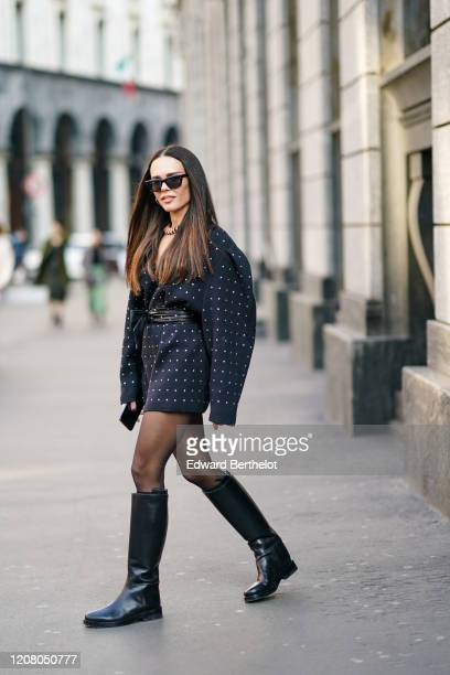 Evangelie Smyrniotaki wears sunglasses, a black dress with printed polka dots, black leather boots, outside Philosophy, during Milan Fashion Week...