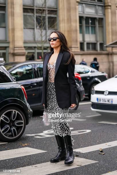 Evangelie Smyrniotaki wears sunglasses, a black oversized blazer jacket, a bejeweled mesh dress, black leather boots, outside Paco Rabanne, during...