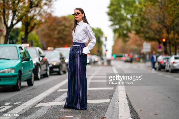 Evangelie Smyrniotaki wears sunglasses a white shirt flare striped blue pants outside Valentino during Paris Fashion Week Womenswear Spring/Summer...