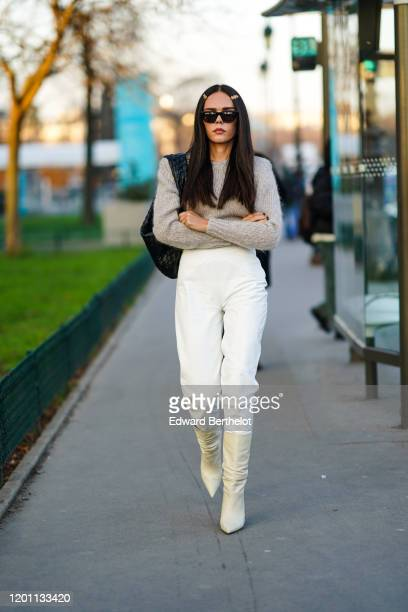 Evangelie Smyrniotaki wears sunglasses, white leather pants, a beige knit sweater, a black woven leather bag, hair clips, beige pointy heeled...