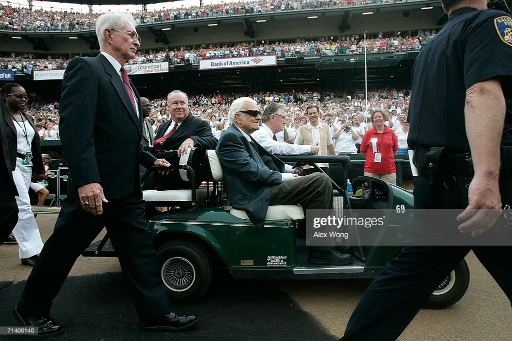 Evangelist Billy Graham (C) arrives in small cart to give the final message of the Metro Maryland 2006 Festival July 9, 2006 at Oriole Park at Camden Yards in Baltimore, Maryland. Franklin Graham, son of Billy Graham, led the three-day-program filled with music, prayers and gospel messages.