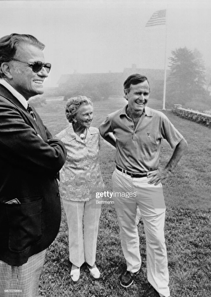 Evangelist Billy Graham, Dorothy Walker Bush, and George Bush smile for the media as Graham arrived here for a weekend visit with the Bush family. Thick fog greeted the evangelist as he arrived at the Walker Point complex, the Bush family's summer estate here.