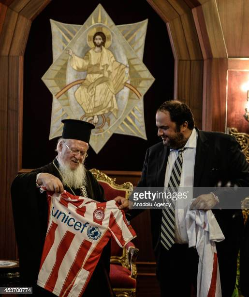 Evangelos Marinakis president of Olympiacos FC gives his team's uniform to Patriarch Bartholomew at Ecumenical Patriarchate ahead of a friendly match...