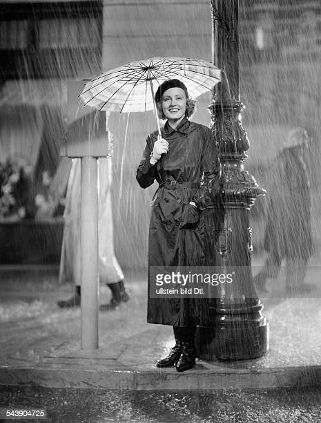 Evans Madge Actress USA* with an umbrella in a picture by MetroGoldwynMayer wearing a navy blue rubberized silk raincoat and a white transparent...