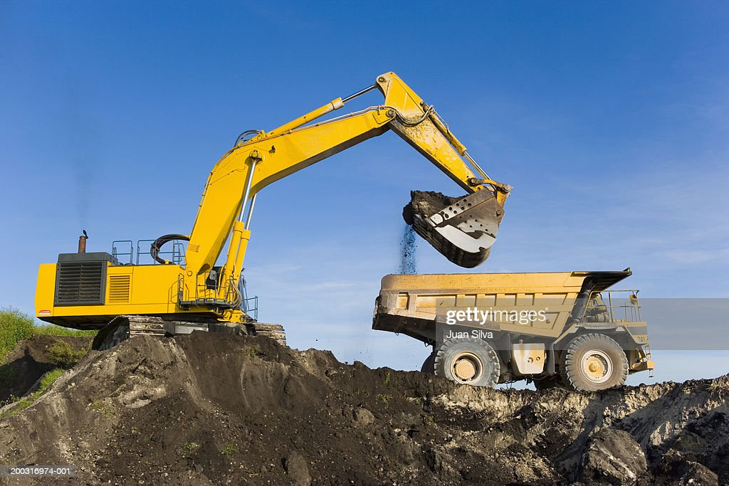 Evcavator and dump truck : Stock Photo