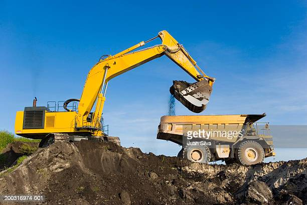 evcavator and dump truck - excavator stock photos and pictures