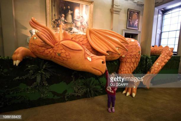 Eve, aged 3, plays with a model of a sleeping dragon in the hall of Chatsworth House which has been decorated for their Christmas season in various...