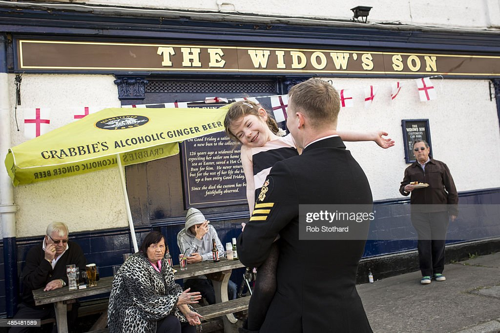 Eve Allen dances with her father Petty Officer Darbz Allen outside the Widow's Son pub in Bromley-by-Bow on April 18, 2014 in London, England. The Widow's Son was built in 1848 upon the former site of an old widow's cottage who, when her only son left to be a sailor, promised to bake him a Hot Cross Bun and keep it for his return. The son never returned but the widow refused to give up hope, baking a fresh one each year. This annual tradition has been continued in the pub as a remembrance of the widow and her son, and of the bond between all those on land and sea, with sailors of the Royal Navy coming to place the bun in a net above the bar.