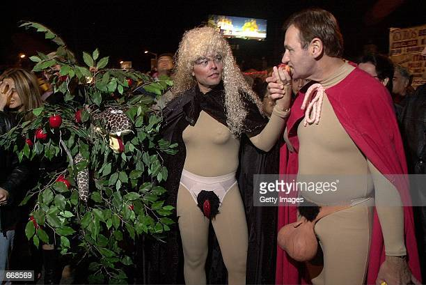 'Eve' gives 'Adam' a bite of her apple during the West Hollywood Halloween Carnival along Santa Monica Boulevard on October 31 2000 in Hollywood CA