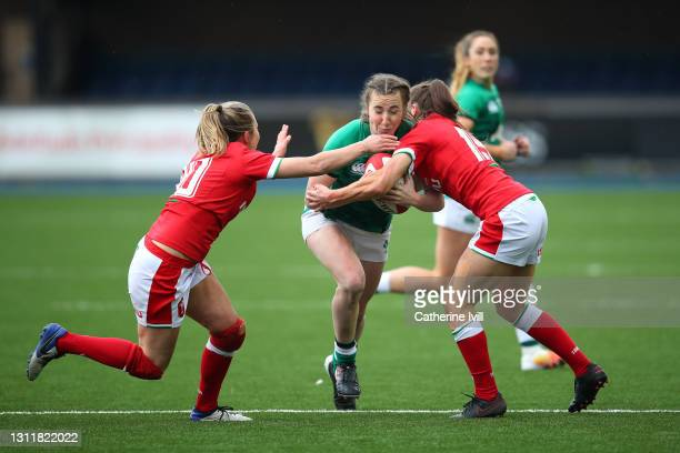 Eve Higgins of Ireland is tackled by Elinor Snowsill and Robyn Wilkins of Wales during the Women's Six Nations match between Wales and Ireland at...