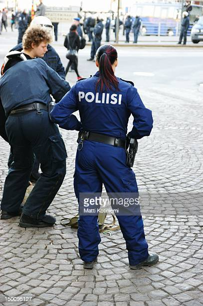 Little demonstration against capitalism in Helsinki. Young policewoman watching as officers in riot gear perform a search on arrested protestor.