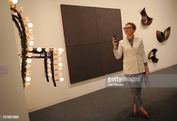 Evelina Khromtchenko looks at the art in a gallery as Art Basel opens at the Miami Beach Convention Center on December 5 2012 in Miami Beach Florida...