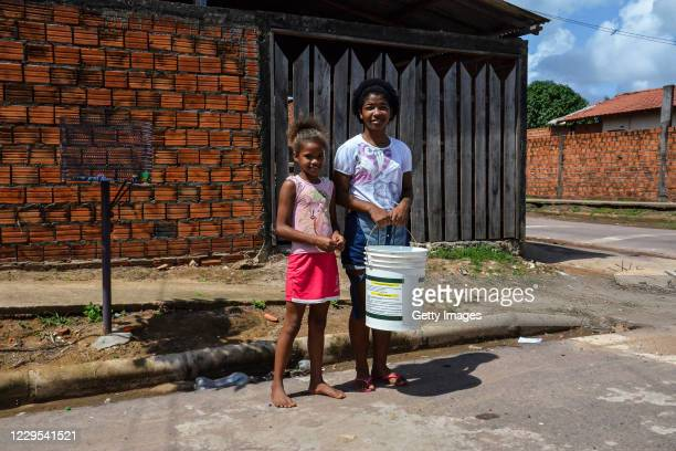 Evelyn and Agata carry water from their neighbors during a blackout due to the fire in the Macapa substation on November 08, 2020 in Macapa, Brazil....