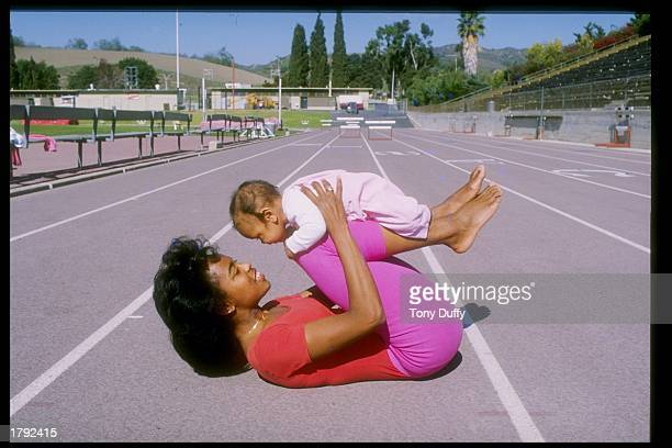 Evelyn Ashford lies on a track and plays with a baby Mandatory Credit Tony Duffy /Allsport