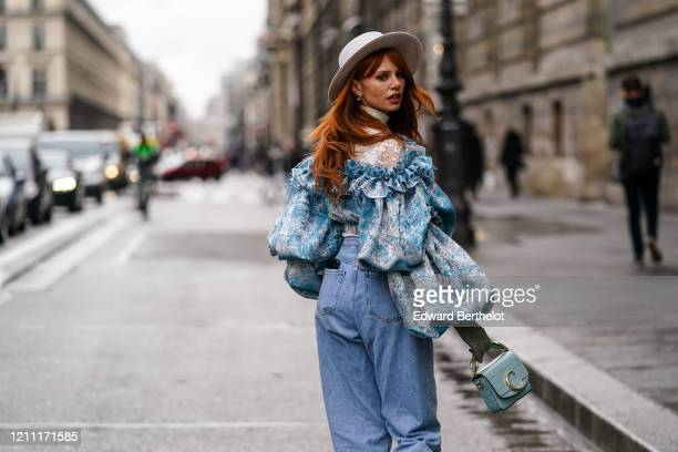 Evelyn Kazantzoglou wears a light grey hat, a frilly blue jacket with a white lace upper part and ruffled puff sleeves, blue jeans, a blue Chloe...