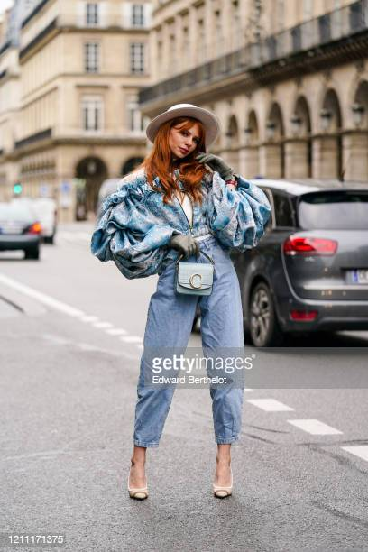Evelyn Kazantzoglou wears a light grey hat, a white turtleneck, a frilly blue jacket with a white lace upper part and ruffled puff sleeves, blue crop...