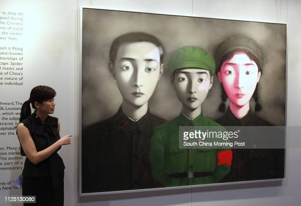 Evelyn Lin Head of the Contemporary Chinese Art Department Sotheby's China and Southeast Asia stands in front of the Zhang Xiaogang Bloodline The Big...