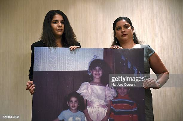 Evelyn Selimaj left of East Haven and her sister Sybelle Almodovar of North Guilford hold a photograph of themselves together with their brother...