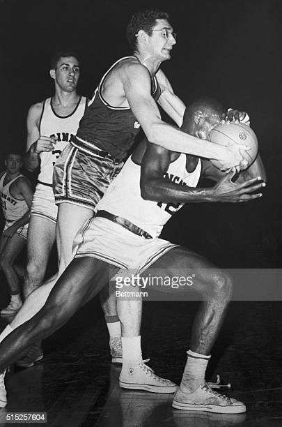 Even getting the ball pushed in his face doesn't stop Cincinnati's dynamic Oscar Robertson from setting another record here, Feb. 8. Robertson, shown...