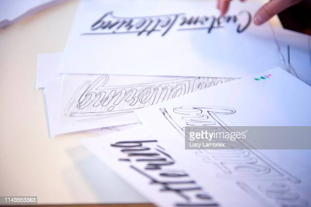 even the expert makes mistakes: some sheets with hand lettering in progress - calligraphy stock photos and pictures