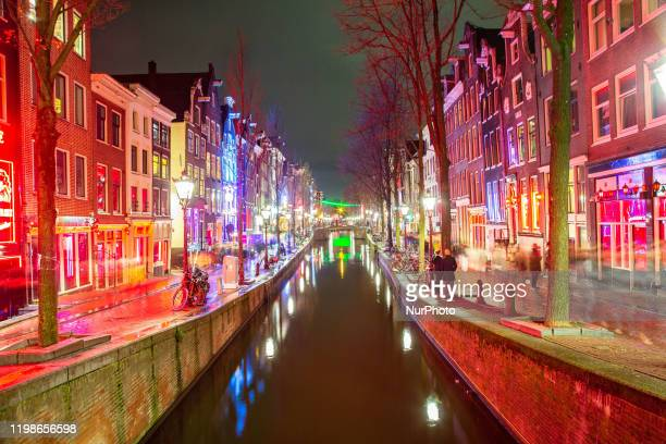 Evening at Amsterdam Red Light District by the canal and reflection of illuminating houses at night in the old part of the city in North Holland the...