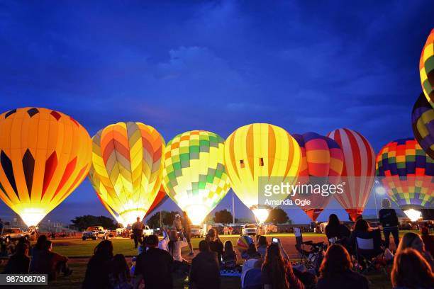 evening balloon glow - balloon fiesta stock pictures, royalty-free photos & images
