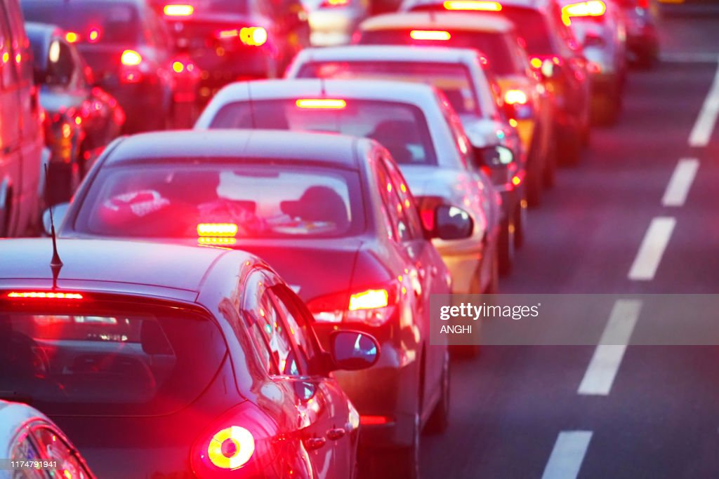 Evening, city traffic jams, street road. Standing in a row cars, rear view, red stop lights. Dividing strip : Stock Photo